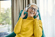 Senior woman sitting in armchair, listening music with headphones - ZEDF02412