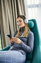 Woman sitting in armchair, listening music with headphones, using smartphone - ZEDF02415