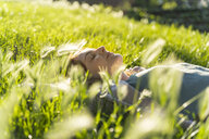Young redheaded woman lying on meadow in a park - AFVF03173