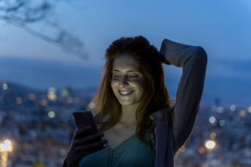 Young woman using smartphone on a view point at blue hour, Barcelona, Spain - AFVF03236