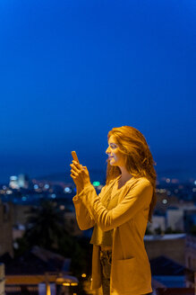 Young woman using smartphone on a view point at blue hour, Barcelona, Spain - AFVF03242