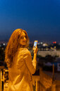 Young woman using smartphone on a view point at blue hour, Barcelona, Spain - AFVF03245