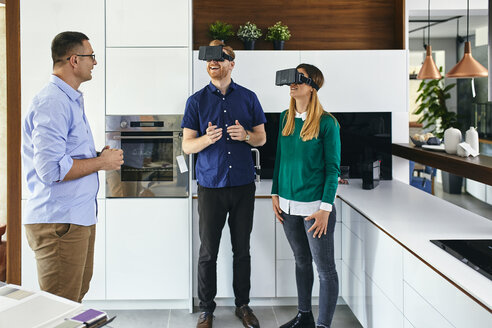 Couple wearing VR glasses shopping for a new kitchen in showroom - ZEDF02440