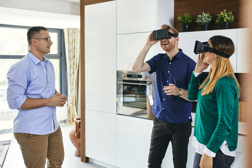 Couple wearing VR glasses shopping for a new kitchen in showroom - ZEDF02443