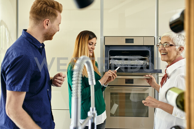 Shop assistant explaining oven to couple shopping for a new kitchen in showroom - ZEDF02449 - Zeljko Dangubic/Westend61