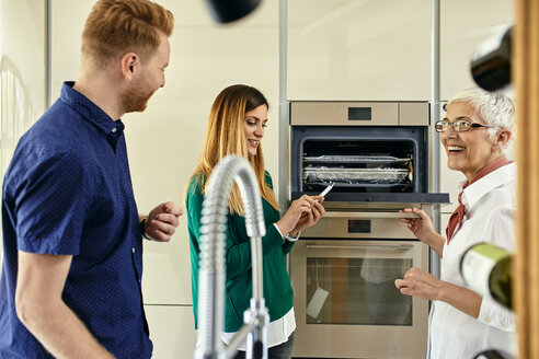Shop assistant explaining oven to couple shopping for a new kitchen in showroom - ZEDF02449