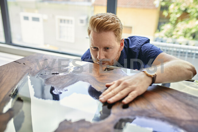 Man examining acrylic resin table in a furniture showroom - ZEDF02467
