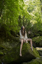 Young woman sitting on a rock in the forest, Garrotxa, Spain - AFVF03255