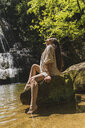 Young woman sitting on rock at a waterfall, Garrotxa, Spain - AFVF03261