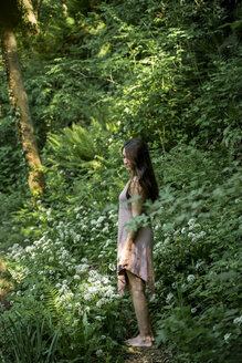 Young woman standing on a path in a lush forest, Garrotxa, Spain - AFVF03267