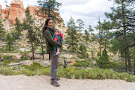 Woman carrying her daughter in a baby carrier at hoodoos in Bryce Canyon, Utah, USA - GEMF02980