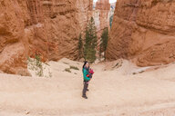 Woman carrying her daughter in a baby carrier at hoodoos in Bryce Canyon, Utah, USA - GEMF02983