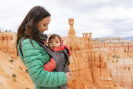 Woman carrying her daughter in a baby carrier at hoodoos in Bryce Canyon, Utah, USA - GEMF02986