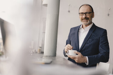 Portrait of mature businessman with coffee cup in a cafe - KNSF05897
