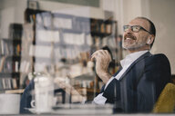 Happy mature businessman listening to music with bluetooth earbuds in a cafe - KNSF05909