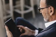 Mature businessman using tablet - KNSF05912
