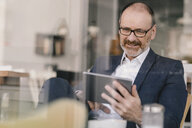 Smiling mature businessman using tablet in a cafe - KNSF05915