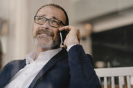 Portrait of mature businessman on cell phone in a cafe - KNSF05918