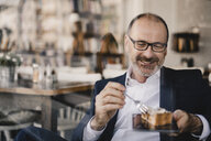 Mature businessman having a piece of cake on a digital tablet in a cafe - KNSF05921