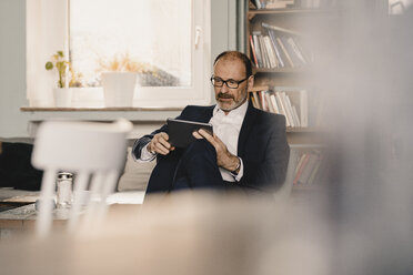 Mature businessman using tablet in a cafe - KNSF05939