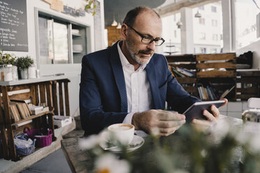 Mature businessman using tablet in a cafe - KNSF05951