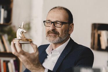 Mature businessman holding a unicorn figurine - KNSF05960