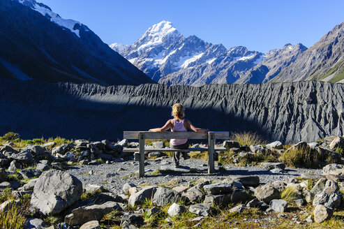 Woman stiitng on a bench and enjoying the view of Mount Cook, South Island, New Zealand - RUNF02459