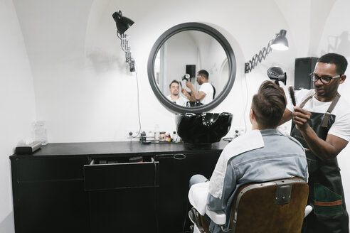 Barber doing hair of a customer in barber shop - AHSF00497