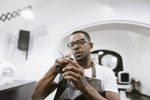 Portrait of barber with scissors in a barber shop - AHSF00503