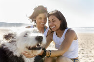 Happy female friends with dog on the beach - MGOF04070