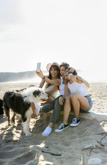 Happy female friends with dog taking a selfie on the beach - MGOF04073
