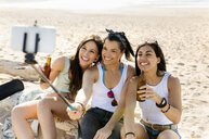Happy female friends with beer bottles taking a selfie on the beach - MGOF04076