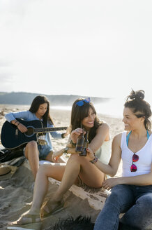 Young woman with friends playing guitar on the beach - MGOF04085
