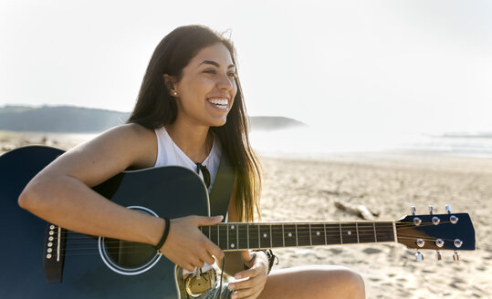 Happy young woman with guitar on the beach - MGOF04091