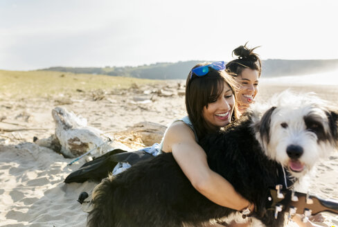Two happy women with dog on the beach - MGOF04094