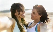 Portrait of two happy female friends on the beach - MGOF04103