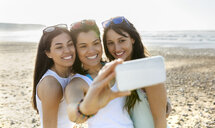 Portrait of happy female friends taking a selfie on the beach - MGOF04106