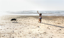 Three women with dog walking on the beach - MGOF04109