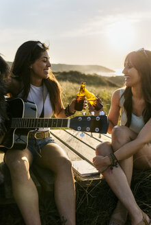 Two happy women with guitar clinking beer bottles on boardwalk in dunes - MGOF04115