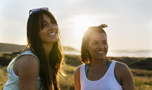 Portrait of two happy female friends in dunes at sunset - MGOF04118