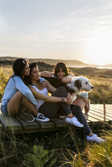 Three happy women with dog sitting on boardwalk in dunes at sunset - MGOF04124