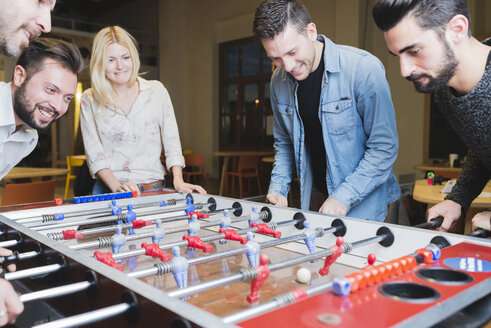 Happy colleagues playing foosball in office - FMOF00685