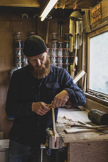 Bearded man wearing black beanie standing at workbench in workshop, working on piece of wood. - MINF11282