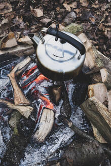 High angle close up of metal kettle hanging over a campfire. - MINF11432