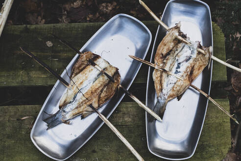 High angle close up of grilled fish on wooden skewers on metal plates, cooking outdoors - MINF11438