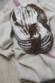 High angle close up of a freshly baked loaf of brown bread on tea towel. - MINF11549