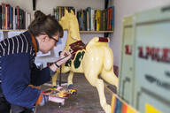 Woman standing in workshop, painting a traditional wooden carousel horse from merry-go-round. - MINF11576