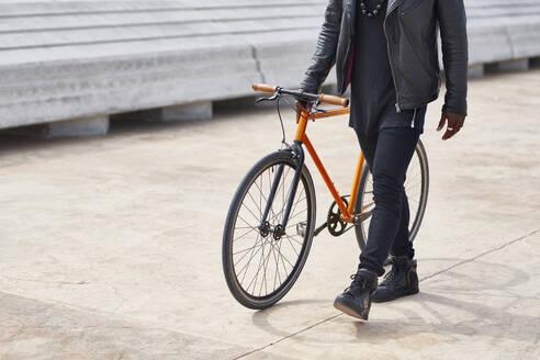 Man with bike on waterfront promenade - JND00046
