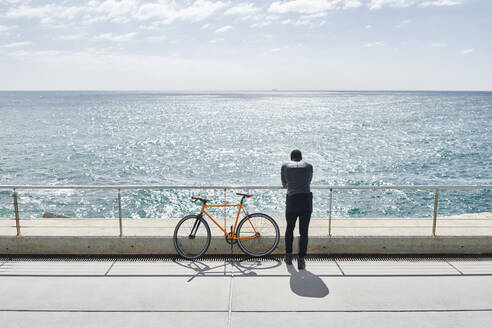 Rear view of man with bike on waterfront promenade - JND00052