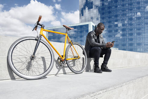 Man with yellow bicycle sitting on stairs, using smartphone, Barcelona, Spain - JND00055